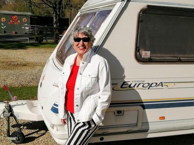 Karen enjoys the sunshine beside her beloved caravan