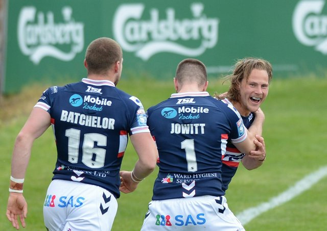 Happy return: Wakefield Trinity's Jacob Miller celebrates after scoring a try on his return from injury, with Max Jowitt and James Batchelor.  Picture: Dean Williams